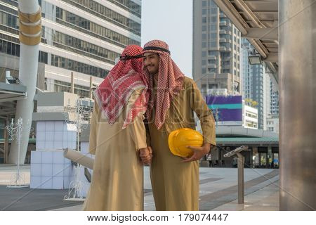 Two young Arab businessmen shake hands in the city.