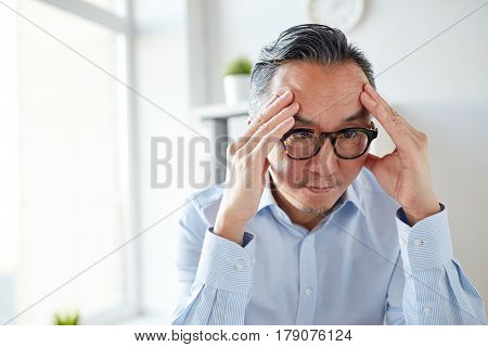 business, overwork, stress, deadline and people concept - anxious businessman in eyeglasses at office