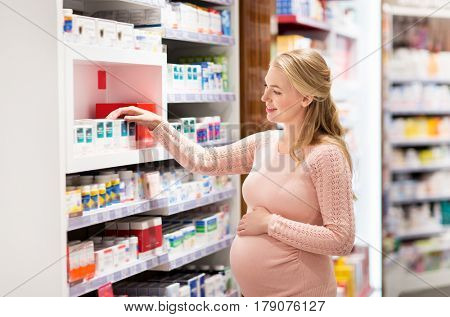 pregnancy, medicine, people, healthcare and expectation concept - happy pregnant woman looking for medication at pharmacy