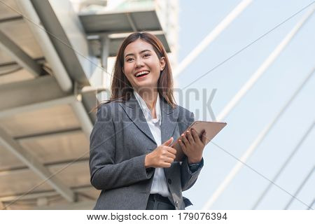 Businesswoman holding tablets and laughing happily in the city.