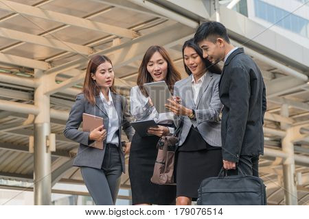 Business team looking at the tablet together rejoicing in their success.