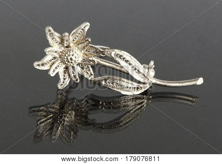 Vintage filigree silver brooch Flower Edelweiss on gray background with mirror reflection