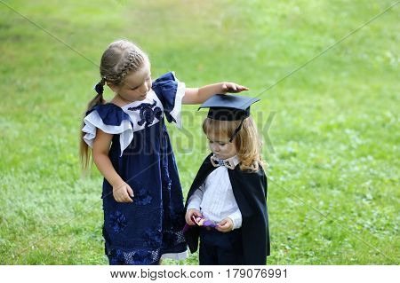 Cute Girl Dressing Small Boy In Graduation Hat And Robe