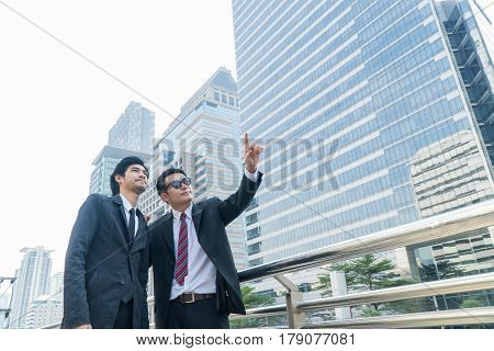 Two young businessmen talking and pointing at something while standing within the city.