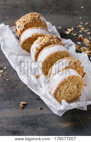Set of homemade ice cream sandwiches in oat cookies with almond sugar crumbs on baking paper over dark metal texture background. Close up