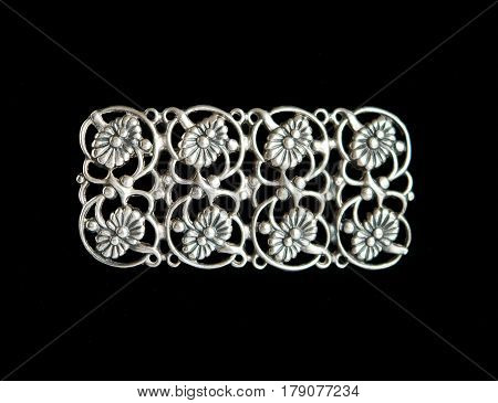 Vintage openwork silver brooch isolated on black background
