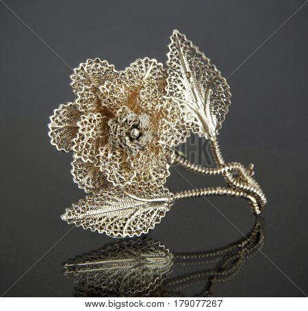 Vintage filigree silver brooch Flower on gray background with mirror reflection