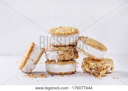 Set of homemade ice cream sandwiches in oat cookies with almond sugar crumbs over gray texture background. Copy space