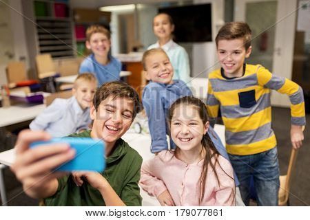 education, elementary school, children and people concept - group of kids taking selfie with smartphone in corridor