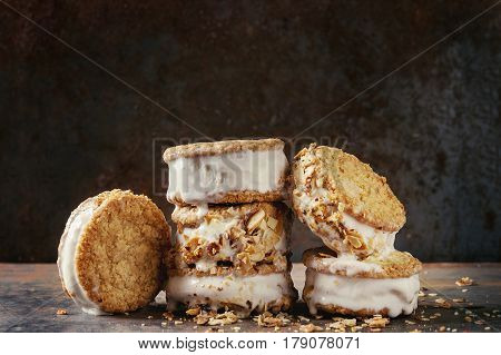 Set of homemade ice cream sandwiches in oat cookies with almond sugar crumbs over dark metal texture background. Close up