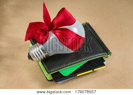 Black wallet with credit cards, green inside. Bulb whith red ribbon on the wallet. Idea for business