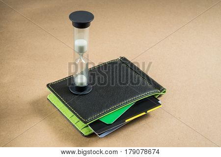Black wallet with credit cards, green inside. Hourglass on the wallet. Time is money