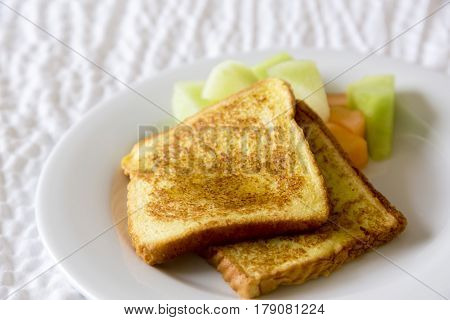 Two slices of French Toast placed with melon in horizontal photograph. Brown tasty breakfast with healthy honeydew and cantaloupe.