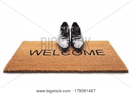 Pair of shoes on a doormat with the word welcome written on it isolated on white background