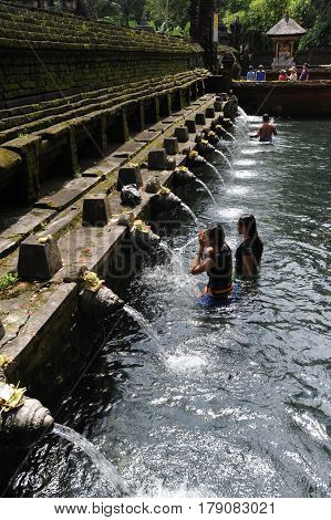 Bali, Indonesia - 12 February 2013 : Travellers praying and take a bath at holy spring water at Tirta Empul Hindu Temple Bali ,Indonesia. They believe that water can bring good health and good luck.