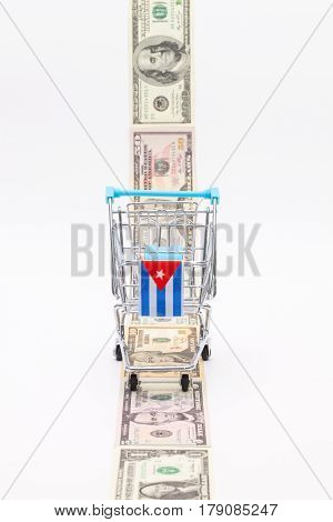 Strip of different us dollar banknotes and empty shopping trolley as a symbol of the american blockade in Cuba