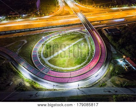 Night scene of transportation infrastructure at T-junction with the overpass aerial view Thailand