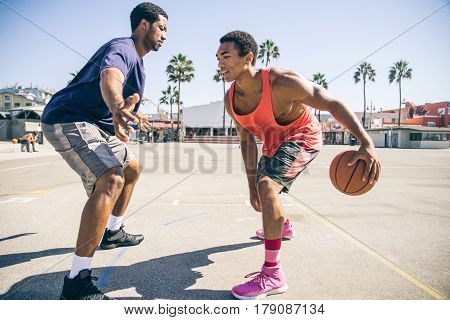 Friends playing basketball - Afro-american players having a friendly match outdoors