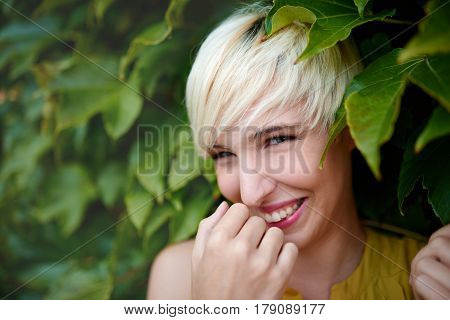 Portrait of an urban boyish blonde millennial girl having a cute, shy laugh and being flirty in front of a leafy background.