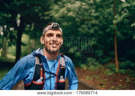 Competitive, athletic young man with a head mounted flashlight runs off road outdoors through the woods on a trail in the afternoon wearing sportswear.