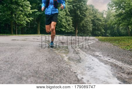 Leg detail of a competitive, athletic young man running off road outdoors through the woods in mud and water puddles on a trail in the afternoon wearing sportswear.