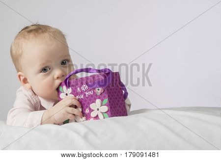 Cute 8 month boy with a gift in a pocket lying on the white blanket and looking at camera. Postcard for mothers day. Copy space. Useful for any holiday