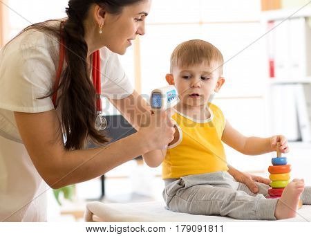 doctor measuring temperature cute kid in hospital