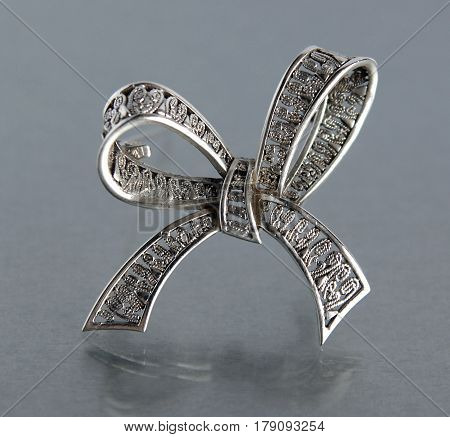 Vintage filigree silver brooch Bow on gray background with mirror reflection