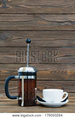 The french press filled with the tea and the white cup on a wooden surface.