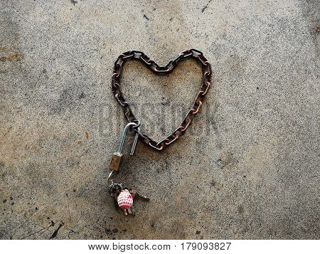 Detail old chain heart-shaped with brass padlock and many key on cememt floor for background