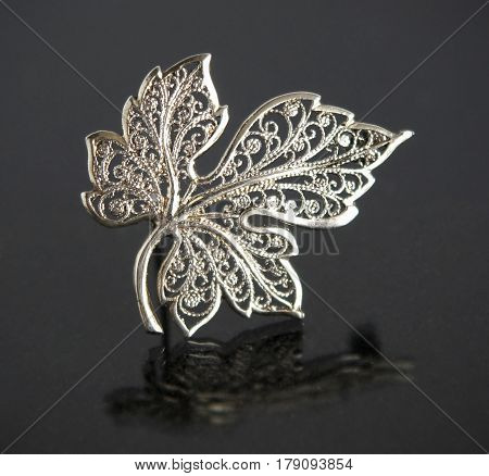 Vintage filigree silver brooch Grape leaf on gray background with mirror reflection