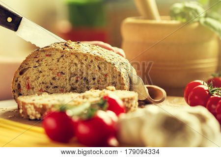 Process of cutting wholewheat bread in the kitchen. Kitchen Background. Cooking process. Toned.