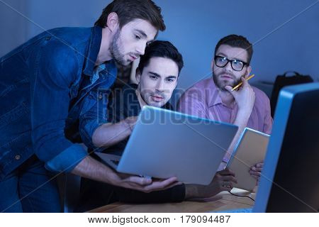 Team of programmers. Attractive brutal intelligent man holding a laptop and showing something to his colleagues while working in team