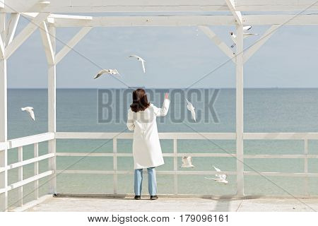 Young woman (brunette) in a white coat feeds the gulls on the beach. Selective focus.
