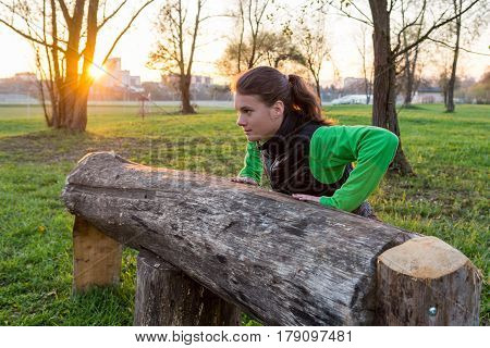 Attractive brunette working out in a park. Pushups at wooden bench.