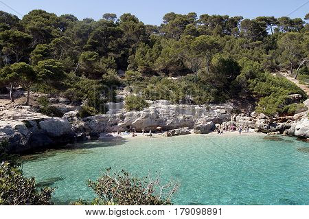 Typical Menorca beach surrounded by greenery cliffs and turquoise waters.