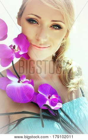 Beautiful woman with long blonde hair and green eyes wearing summery golden makeup and a torqouise dress is posing with a bright fuchsia coloured orchid close to her face.