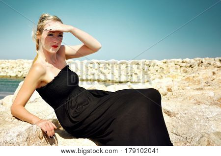 Young blonde attractive woman wearing a long black maxi dress and red lipstick sitting on the rocks by the sea and is holding her hand above her eyes to look far into the distance.