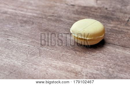 yelow macaroon on wooden table with vintage effect