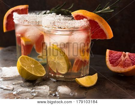 Nonalcoholic drink cocktail of fresh fruits: grapefruit, lime, rosemary concept of a healthy drink. Rusty metal background