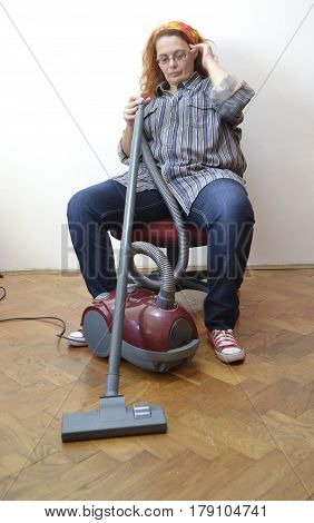 Housewife with vacuum cleaner rest from hard work