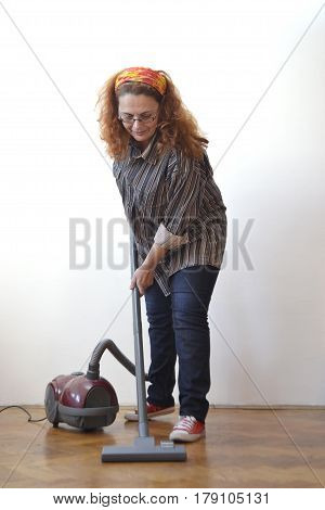 Housewife with vacuum cleaner cleaning floor - front view