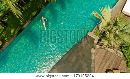 Beautiful sexy woman relaxed in pool after spa having fun at her vacation in luxury resort