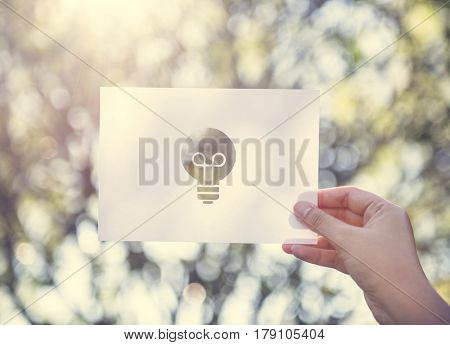 Human hand holding light bulb perforated paper craft in nature