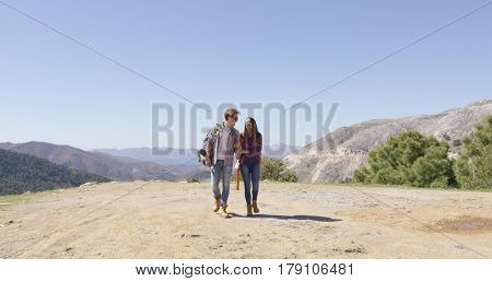 Romantic couple walking on plat of mountain and talking with amazing view on background in summer.