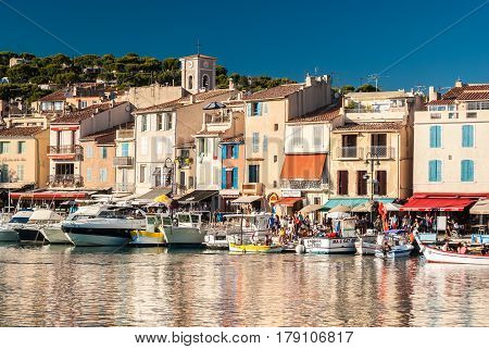 CASSIS FRANCE - AUGUST 24 2016: The crowded promenade of Cassis a small touristic town in southern France with many restaurants and shops during a summer afternoon