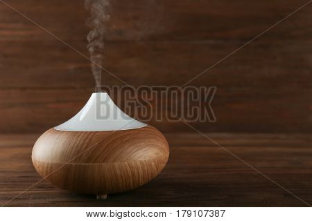 Aroma oil diffuser on wooden background