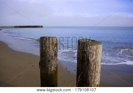 Two old wooden pylons on the beach.