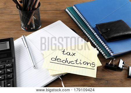 Paper sheet with text TAX DEDUCTIONS, calculator and open notebook on wooden table