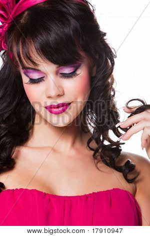 Portrait of beautiful girl with dark hair wearing pink on white